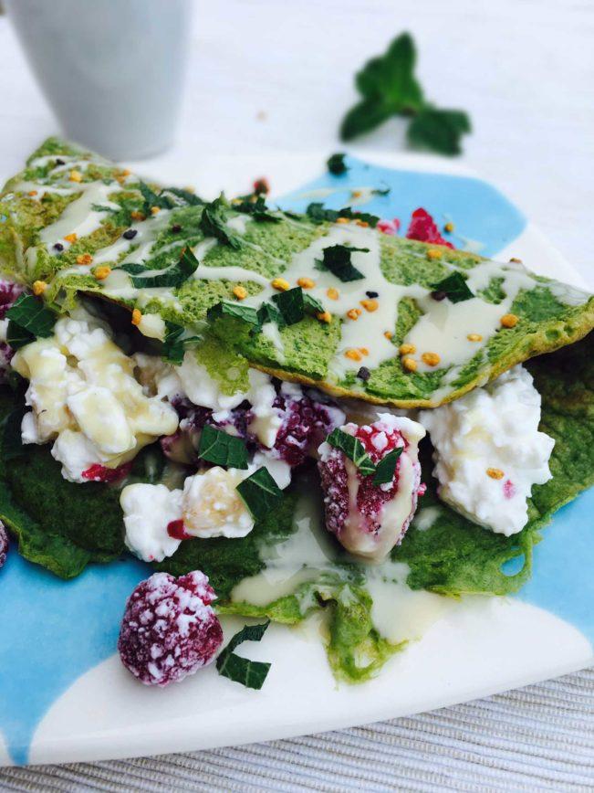 Spinatpandekage med hytteost og hindbær. Lækker, smuk og mættende morgenmad med masser af protein. Udover den gode smag vil du mærke, hvordan den holder dig mæt langt op ad dagen. Nem opskrift her: Madbanditten.dk