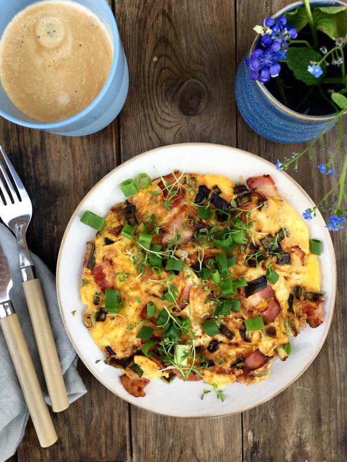 Omelet med bacon, ost og forårsløg - lækker low carb morgenmad. Opskrift her: Madbanditten.dk